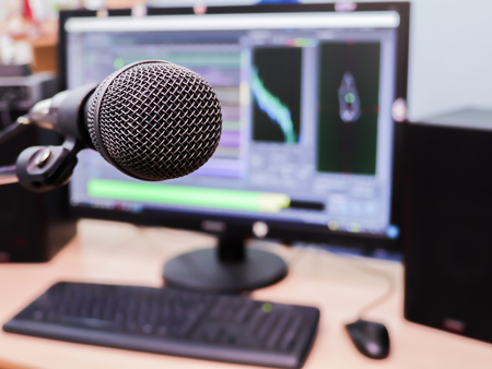 cardioid: Microphone on the background of the computer monitor. Home recording Studio. Close-up. The focus in the foreground. Blurred background. Software for recording and editing sounds.