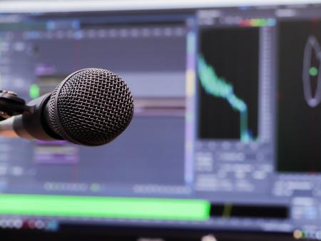 cardioid: Micrófono en el fondo del monitor de la computadora. Estudio de grabación en casa. De cerca. El foco en primer plano. Fondo borroso. Software para grabación y edición de sonidos.