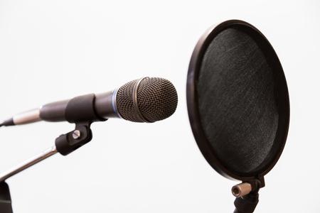cardioid: Micrófono condensador cardioide y filtro pop sobre fondo gris. Estudio de grabación casera. Foto de archivo