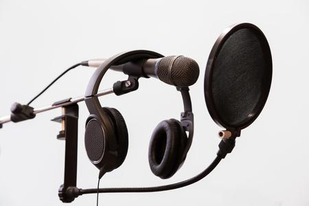 cardioid: Micrófono de condensador cardioide, auriculares y filtro pop sobre un fondo gris. Estudio de grabación casera.