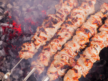Cooking kebab on the coals. Grilled pork on skewers. Stock Photo