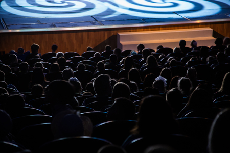 People, children, adults, parents in the theater. People in the auditorium looking at the stage. Shooting from the back