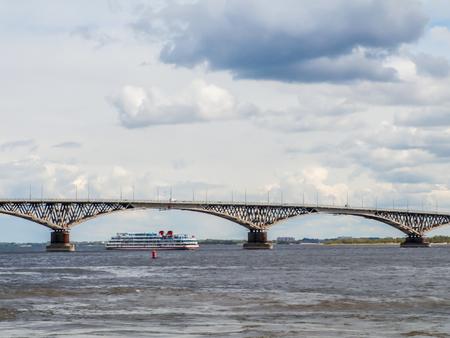 riverbank: River passenger ship Simeon Budyonny passes under the road bridge. Russia, Saratov, 3 Jun 2017 Editorial