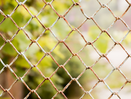 Rusty colored mesh netting. The metal fence.