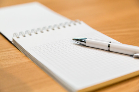 A notebook and ballpoint pen lying on a wooden table. Stock Photo