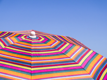 Colorful beach umbrella against the blue sky. Striped texture Stock Photo