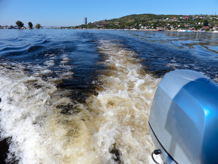 outboard: Outboard motor. Summer river landscape, photographed from the side of the boat. Russia, Saratov, the Volga river. Road bridge between the cities of Saratov and Engels.