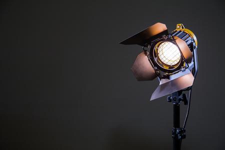 Proiettore con lampada alogena e lente di Fresnel su sfondo grigio. Apparecchiature di illuminazione per le riprese. Riprese e fotografie negli interni. Archivio Fotografico - 82740931