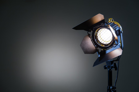 Floodlight with halogen lamp and Fresnel lens on a gray background. Lighting equipment for shooting. Filming and photographing in the interior. Banco de Imagens - 82740934