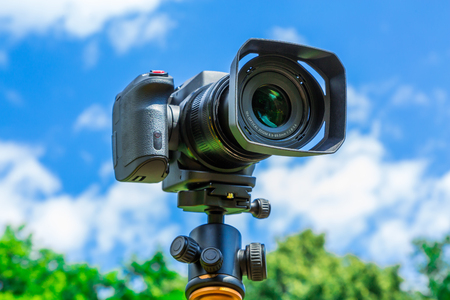 Digital camera closeup on a background of sky and clouds. Shooting on location and nature. Stok Fotoğraf