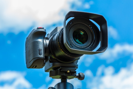 Digital camera closeup on a background of sky and clouds. Shooting on location and nature. Banco de Imagens - 82917773