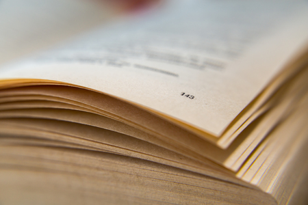 Open old book. Yellowed pages. Page number 143. Paper texture. Macro.