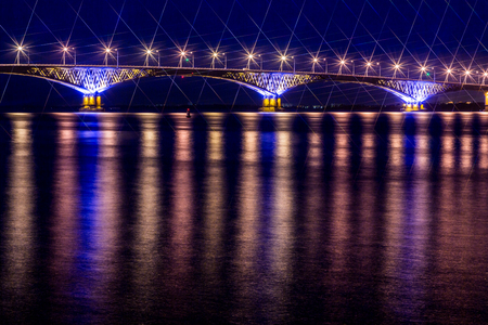 Road bridge across the Volga river between the cities of Saratov and Engels, Russia. Night or evening landscape. Golden street lights. The reflection in the water.