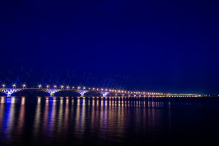 street lamp: Road bridge across the Volga river between the cities of Saratov and Engels, Russia. Night or evening landscape. Golden street lights. The reflection in the water.