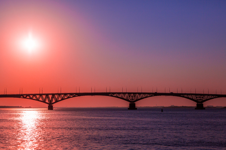 Sunrise over a road bridge across the Volga river between the cities of Saratov and Engels, Russia. Stock Photo