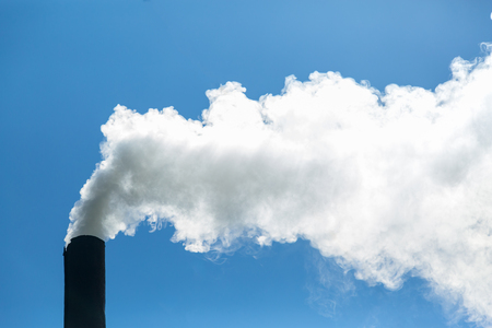 White smoke comes from the chimney on the background of blue sky. Air pollution and the environment. The greenhouse effect. Environmental disaster