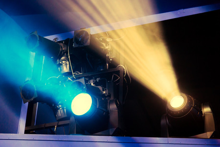 Lighting equipment on the stage during the performance. The light from the spotlight through the smoke. Blue and yellow rays of light. Stockfoto