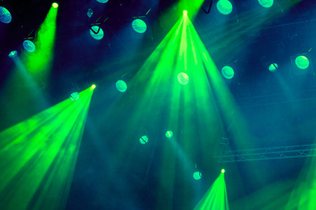 nightspot: Lighting equipment on the stage during the performance. The light from the spotlight through the smoke. Green rays of light