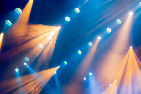 nightspot: Lighting equipment on the stage during the performance. The light from the spotlight through the smoke. Blue and yellow rays of light. Stock Photo