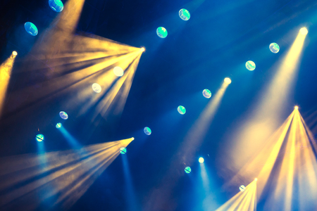 Lighting equipment on the stage during the performance. The light from the spotlight through the smoke. Blue and yellow rays of light. Stock Photo