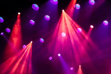 Lighting equipment on the stage during the performance. The light from the spotlight through the smoke. Red and purple beams. Stock Photo