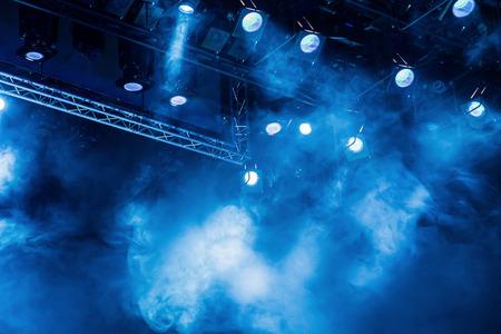 Niebieskie promienie światła od światła reflektorów przez dym w teatrze lub w sali koncertowej. Sprzęt oświetleniowy do spektaklu lub spektaklu. Zdjęcie Seryjne