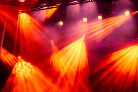 Yellow and red light rays from the spotlight through the smoke at the theater or concert hall. Lighting equipment for a performance or show. Stock Photo