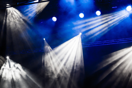 nightspot: White and blue light rays from the spotlight through the smoke at the theater or concert hall. Lighting equipment for a performance or show. Stock Photo
