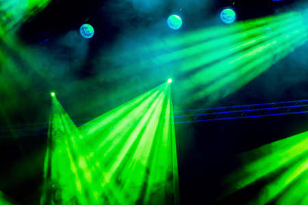Green light from the spotlight through the smoke at the theater or concert hall. Lighting equipment for a performance or show. Stock Photo
