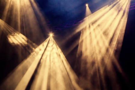 The yellow light from the spotlight through the smoke. Lighting equipment for a performance or show. Stock Photo