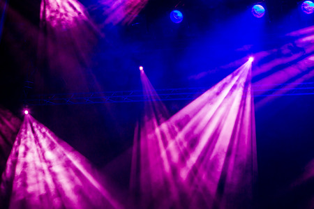 nightspot: Blue and purple rays from the spotlight through the smoke at the theater or concert hall. Lighting equipment for a performance or show. Stock Photo