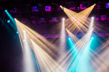 Yellow, white, and blue light from the spotlight through the smoke at the theater or concert hall. Lighting equipment for a show or performance. 스톡 콘텐츠