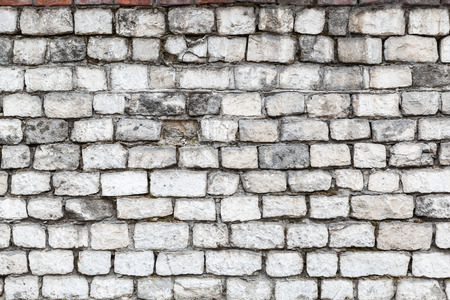 The old stone walls. The brick wall of the house. Gray textured background. Abstraction.