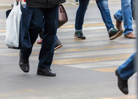 People on a pedestrian crossing. Feet and shoes, asphalt. Stock Photo