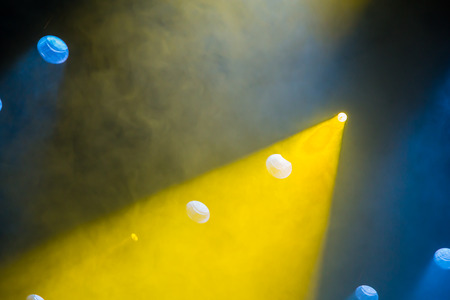 Yellow and blue light rays from the spotlight through theatrical smoke. Lighting equipment on the stage. Stock Photo
