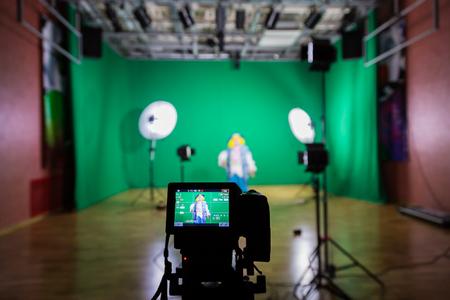 녹색 화면으로 동영상 촬영하기. 크로마 키. 스튜디오 비디오 그래피. 연극 의상을 입은 여배우. 카메라 및 조명 장비.