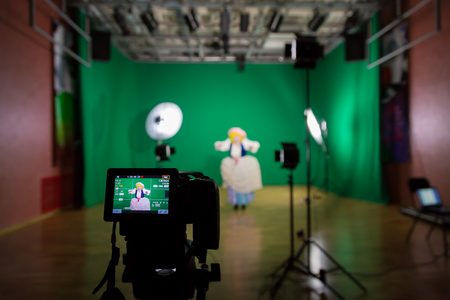 Shooting the movie on a green screen. The chroma key. Studio videography. Actress in theatrical costume. The camera and lighting equipment. Stock fotó