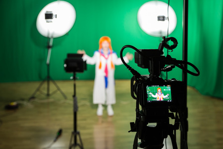 Actress in theatrical costume in a Television Studio. Green screen and chroma key. Lighting equipment and filming equipment.