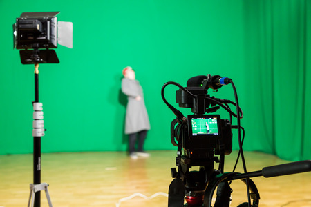 The actor starred in the interior on a green background. The chroma key. Filming equipment. Stock Photo