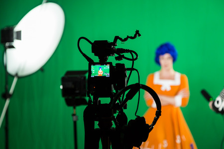 The actress in the studio on a green background. Video of the interview. Cameras and lighting equipment.