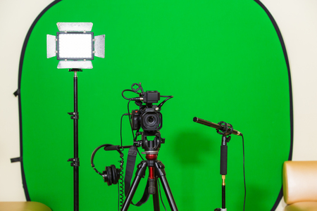 The camera on the tripod, led floodlight, headphones and a directional microphone on a green background. The chroma key. Green screen. Banque d'images