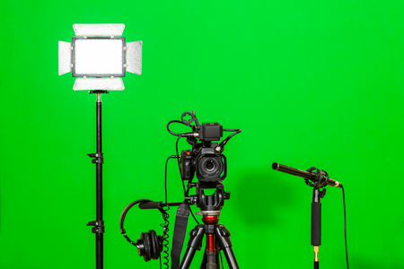 The camera on the tripod, led floodlight, headphones and a directional microphone on a green background. The chroma key. Green screen. 스톡 콘텐츠