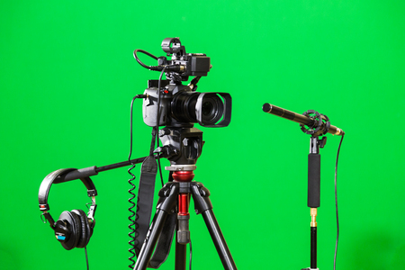 Video camera on a tripod, headphones and a directional microphone on a green background. The chroma key. Green screen. Banque d'images
