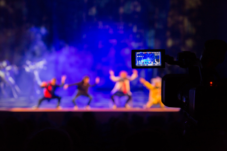 Filming the show from the auditorium. LCD viewfinder on the camcorder. Theatrical performance. The actors on stage. Out-of-focus background. The focus in the foreground.