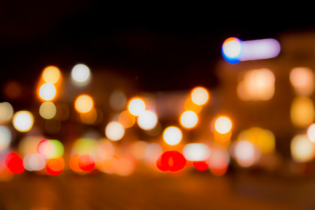 Blurred abstract background. The street lights in a blur. Evening or night city. Light of shop Windows and cars. Stock Photo