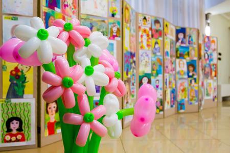 Competitie van kindertekeningen. Tentoonstelling van kinderkunst. Kleurrijke ballonnen op de voorgrond. Onscherpe achtergrond.