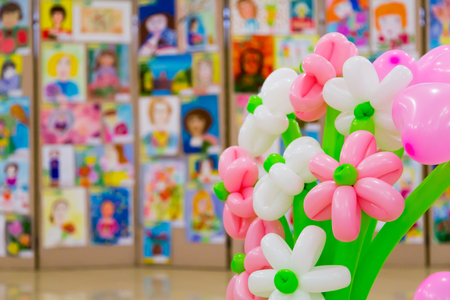 Competition of childrens drawings. Exhibition of childrens art. Colorful balloons in the foreground. Defocused background.