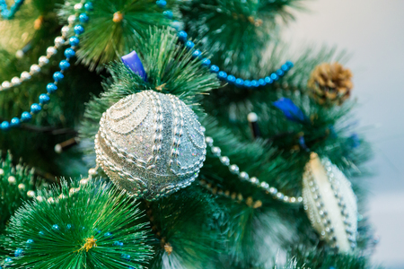 Decorated Christmas tree with blue lights. White Christmas ball and garland.