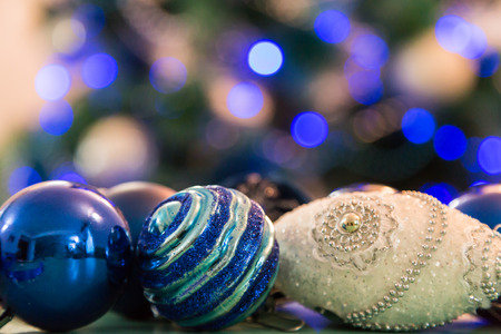 Decorated Christmas tree with blue lights. Christmas balls in the foreground. Blurred image of a tree in the background.