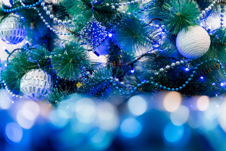 decorated christmas tree with blue lights white christmas ball and garland unfocused image in
